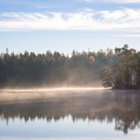 Nuuksio National Park in fall. One of the best times to hike in the national park with fresh air and mist rising from lakes. Nature near Helsinki, Finland.