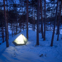 Nuuksio National Park in winter. Hiking and camping with a tent in March. Finnish nature near Helsinki, Finland.