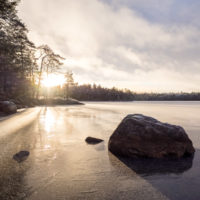 Nuuksio National Park in winter. Hiking at the frozen lakes, snow clouds coming in. Nature near Helsinki, Finland.