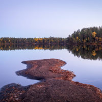 Nuuksio National Park in fall, in October. Calm, clear lake after sunset. Finnish nature near Helsinki, Finland.